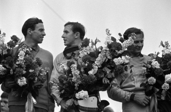 Race winner Jim Clark on the podium with Jackie Stewart, 2nd position, and Bruce McLaren, 3rd position.