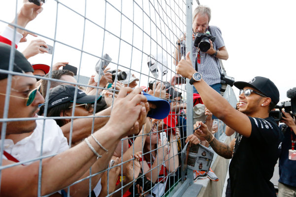 Circuit Gilles Villeneuve, Montreal, Canada. Sunday 7 June 2015. Lewis Hamilton, Mercedes AMG, 1st Position, celebrates with and signs autographs for fans. World Copyright: Alastair Staley/LAT Photographic. ref: Digital Image _79P5769