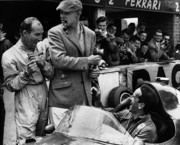 Silverstone, England. 17th - 19th July 1958.Stirling Moss (Vanwall VW10), retired, shares a joke with Mike Hawthorn (Ferrari Dino 246), 7th position, in the pits with a mechanic, portrait. World Copyright: LAT Photographic.Ref: B/W Print.