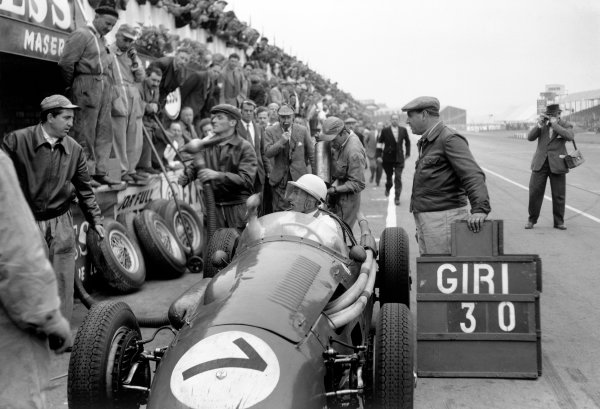 Silverstone, England. 14th July 1956. Stirling Moss (Maserati 250F), 8th position, pit lane with Autosport founding editor John Bolster in the background, talking on a radio microphone, portrait. World Copyright: LAT Photographic Ref: Autocar Glass Plate C47316.