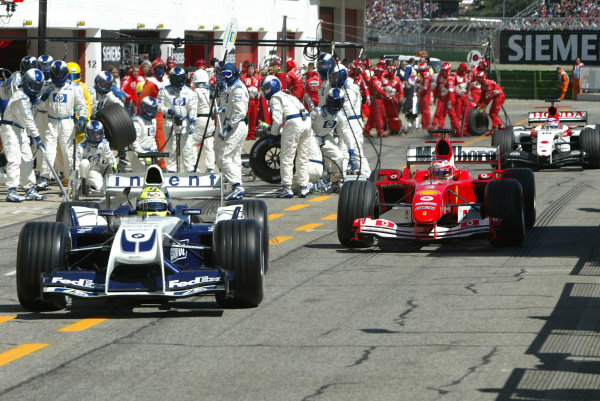2004 San Marino Grand Prix-Sunday Race,Imola, Italy. 25 April 2004.Controversy in the pitlane as Ralf Schumacher is released just in front of Rubens Barrichello in a race for track position. Barrichello is also under scrutiny for exiting his pit in front of Sato.World Copyright: LAT Photographic.Ref: Digital Image only.