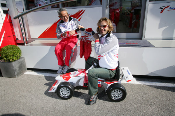 2005 San Marino Grand Prix - Friday Practice,Imola, Italy. 22nd April 2005 Tsutomu Tomita, Chairman of Toyota Racing and Toyota Team Principal presents Jarno Trulli, Toyota TF105, with baby overalls and a mini Toyota car following the birth of Enzo Trulli (ITA)World Copyright: Steve Etherington/LAT Photographic ref: 48mb Hi Res Digital Image Only