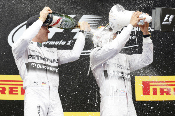 Circuit de Catalunya, Barcelona, Spain. Sunday 11 May 2014. Lewis Hamilton, Mercedes AMG, 1st Position, drinks from his trophy whilst getting blasted with Champagne by Nico Rosberg, Mercedes AMG, 2nd Position. World Copyright: Alastair Staley/LAT Photographic. ref: Digital Image _79P1807
