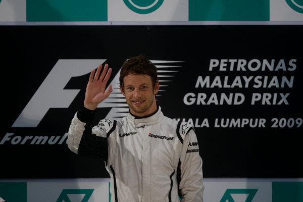 Sepang, Kuala Lumpur, Malaysia 5th April 2009 Jenson Button, Brawn GP BGP001 Mercedes, 1st position, celebrates on the podium. Portrait. Podium.  World Copyright: Andrew Ferraro/LAT Photographic ref: Digital Image _H0Y1269