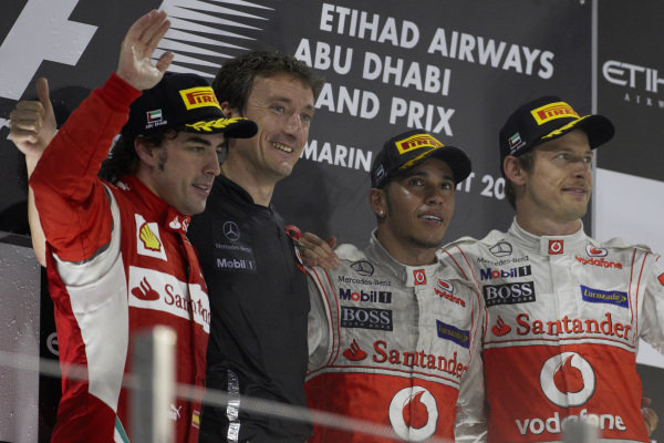 Fernando Alonso, 2nd position, Andy Latham, Lewis Hamilton, 1st position, and Jenson Button, 3rd position, on the podium.