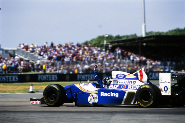 Damon Hill, Williams FW16 Renault, waves to the fans while waving a Union Flag.