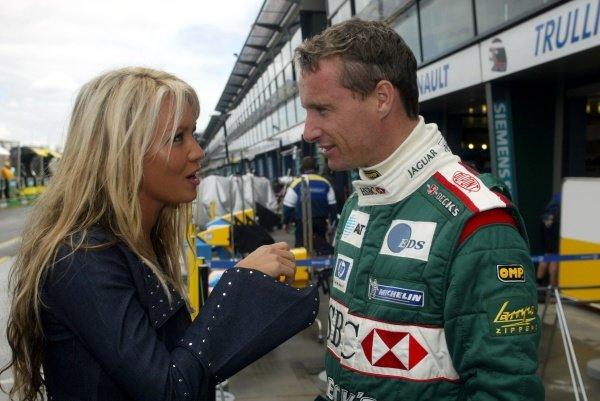 Eddie Irvine (GBR) has a chat with Australian Model Sarah Jane (AUS) in the pit lane. Australian Grand Prix Practice, Albert Park, Melbourne, 1 March 2002 DIGITAL IMAGE