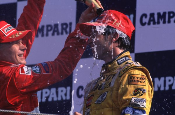 1999 Italian Grand Prix.Monza, Italy.10-12 September 1999.Heinz-Harald Frentzen (Jordan Mugen Honda) celebrates his 1st position on the podium, whilst Mika Salo (Ferrari) 3rd position pours champagne over him.Ref-99 ITA 03.World Copyright - LAT Photographic