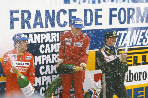 Niki Lauda, 1st position, Patrick Tambay, 2nd position, and Nigel Mansell, 3rd position, celebrate on the podium by spraying champagne.