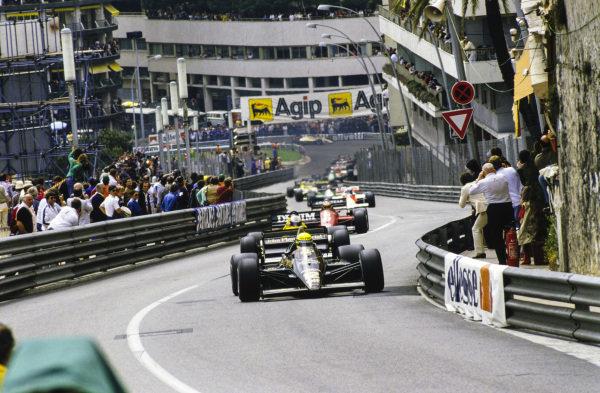 Ayrton Senna, Lotus 97T Renault, leads Nigel Mansell, Williams FW10 Honda, Michele Alboreto, Ferrari 156/85, and Alain Prost, McLaren MP4-2B TAG, up Beau Rivage on the opening lap.