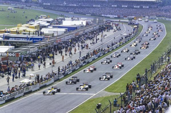 Nelson Piquet, Williams FW11 Honda, pulls away from Nigel Mansell, Williams FW11 Honda, Ayrton Senna, Lotus 98T Renault, and Gerhard Berger, Benetton B186 BMW, at the start.