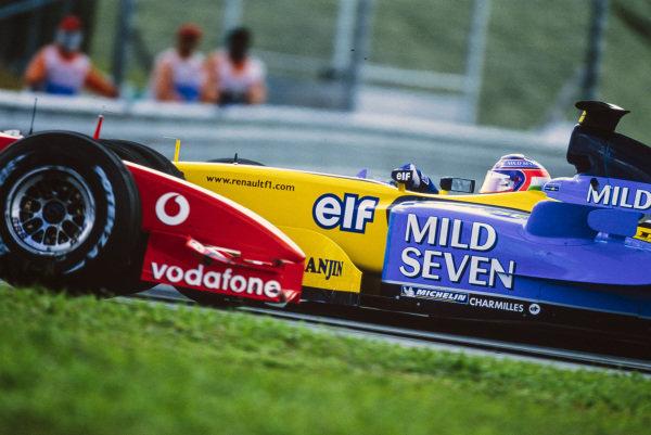 Jarno Trulli, Renault R23, is spun round by Michael Schumacher, Ferrari F2002.