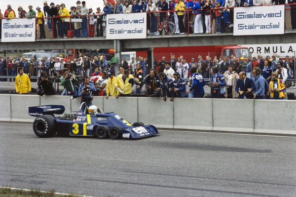 Jody Scheckter pulls up beside designer Derek Gardner and team in his Tyrrell P34 Ford to celebrate his victory. Stirling Moss looks on.