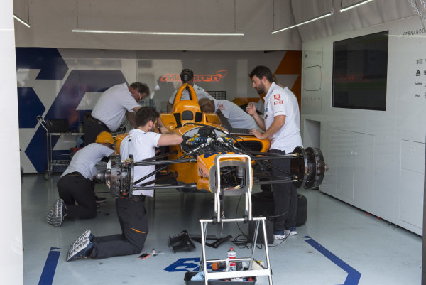 Fernando Alonso, McLaren Racing Chevrolet, crew prepare spare car after accident