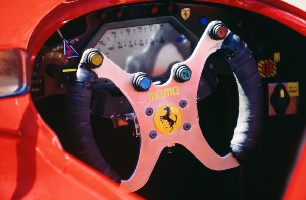Detail view of the Momo steering wheel in the Ferrari 412T2 during practice.