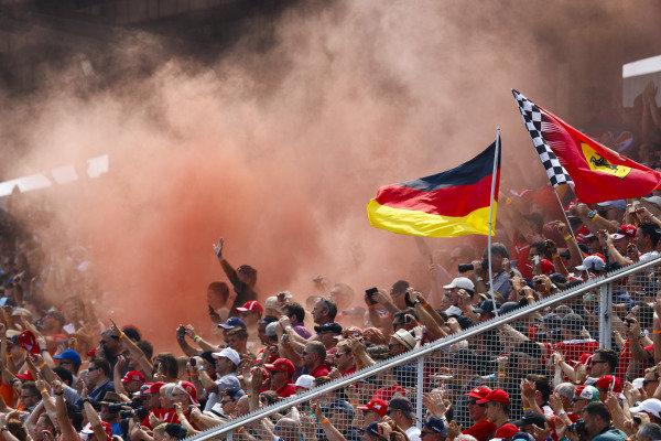 Fans in a grandstand set off flares.