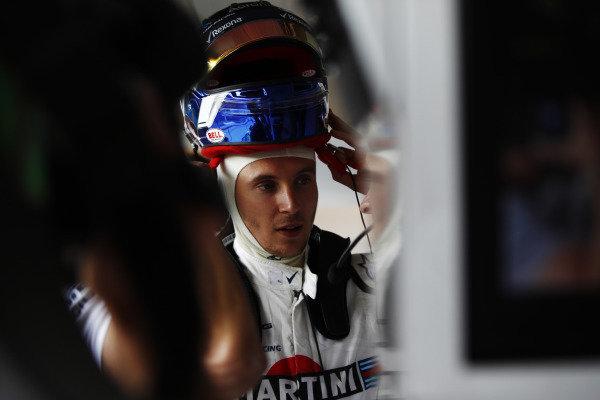 Sergey Sirotkin, Williams Racing, puts on his helmet in the garage.