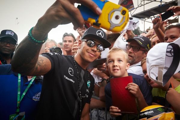 Spa-Francorchamps, Spa, Belgium. Thursday 20 August 2015. Lewis Hamilton, Mercedes AMG, takes a photo with a young fan. World Copyright: Steve Etherington/LAT Photographic ref: Digital Image SNE15048