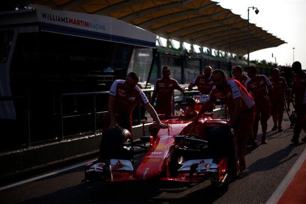 Sepang International Circuit, Sepang, Kuala Lumpur, Malaysia. Thursday 26 March 2015. The Ferrari team pushing Kimi Raikkonen's car down the pit lane. World Copyright: Andrew Hone/LAT Photographic. ref: Digital Image _ONZ7349