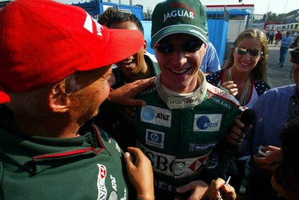 (L-R) Niki Lauda (AUT) Jaguar Team Principal and Eddie Irvine (GBR) Jaguar celebrate a third place finish.Italian Grand Prix Race, Monza, Italy. 15 September 2002.DIGITAL IMAGE