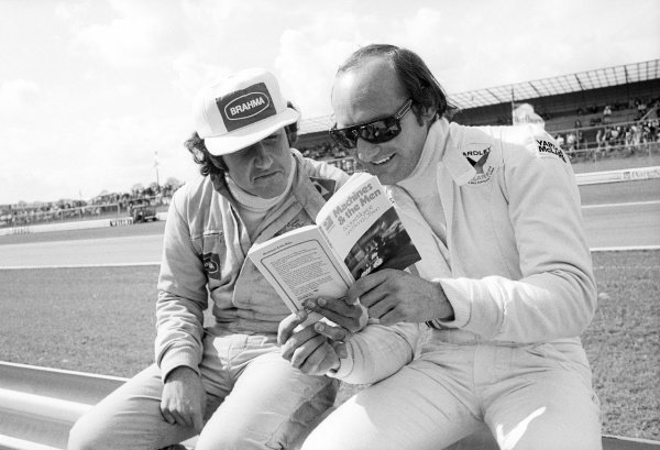 (L to R): Carlos Pace (BRA) Surtees enjoys reading 'Machines & The Men,' a book by Andrew Marriott and Anna O'Brien, with Mike Hailwood (GBR) McLaren.