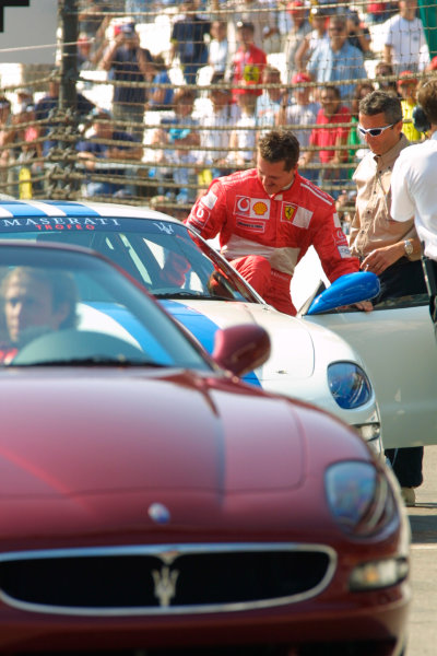 2002 American Grand Prix.Indianapolis, Indiana, USA. 27-29 September 2002.Michael Schumacher (Ferrari) gets into a Maserati Trophy car for a demonstration.World Copyright - LAT Photographicref: Digital File Only