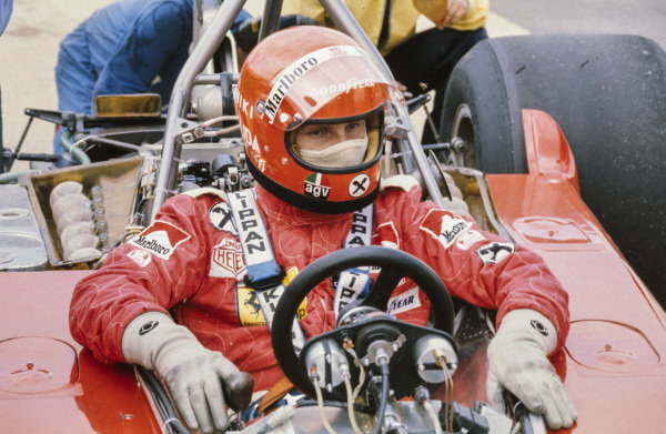 Niki Lauda sat in the cockpit of his Ferrari 312T while mechanics work on the rear.