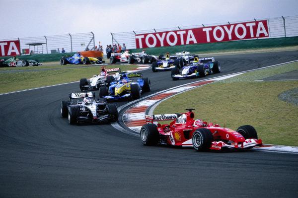 Rubens Barrichello, Ferrari F2004 leads Kimi Räikkönen, McLaren MP4-19B Mercedes and Fernando Alonso, Renault R24.