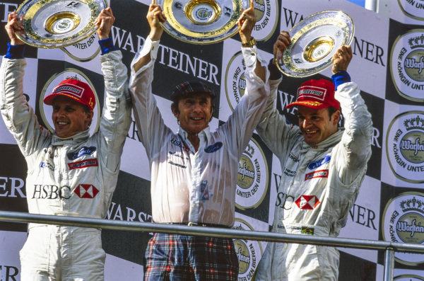Johnny Herbert, 1st position, Jackie Stewart, Team Principal, Stewart Grand Prix, and Rubens Barrichello, 3rd position, celebrate on the podium.