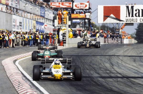 Keke Rosberg, Williams FW09 Honda, leads Riccardo Patrese, Alfa Romeo 184T, and Elio de Angelis, Lotus 95T Renault.
