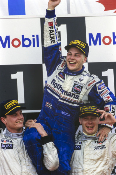 Newly-crowned world champion Jacques Villeneuve, 3rd position, is raised on the podium by Mika Häkkinen, 1st position, and David Coulthard, 2nd position.