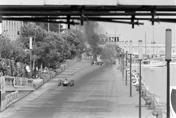 Graham Hill, Lotus 33 BRM, passes the crashed car of Lorenzo Bandini, Ferrari 312.