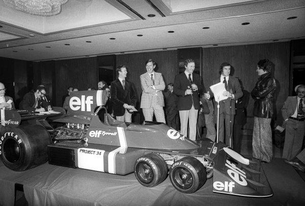 Tyrrell launch their innovative six wheeler Tyrrell Project 34 car, with, on stage, (L to R): ??; Ken Tyrrell (GBR) Tyrrell Team Owner; Derek Gardner (GBR) Tyrrell Designer; Jackie Stewart (GBR); Patrick Depailler (FRA). Tyrrell P34 Launch, England, C. Late 1975.