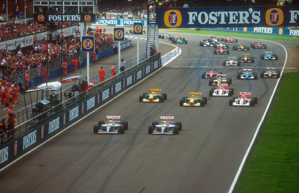 1992 British Grand Prix.Silverstone, England.10-12 July 1992.Riccardo Patrese beats poleman and teammate Nigel Mansell (both Williams FW14B Renault's) away at the start, followed by Michael Schumacher, Martin Brundle (both Benetton B192 Ford's), Ayrton Senna, Gerhard Berger (both McLaren MP4/7A Honda's), Johnny Herbert (Lotus 107 Ford), Jean Alesi (Ferrari F92A), Erik Comas (Ligier JS37 Renault) and Mika Hakkinen (Lotus 107 Ford).Ref-92 GB 08.World Copyright - LAT Photographic