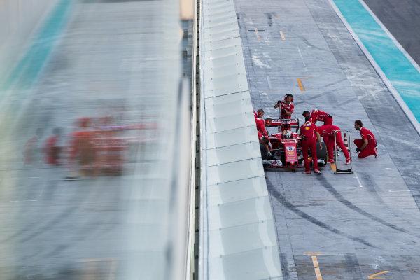 Yas Marina Circuit, Abu Dhabi, United Arab Emirates. Wednesday 29 November 2017. Sebastian Vettel, Ferrari SF70H, is attended to by mechanics in the pit lane. World Copyright: Zak Mauger/LAT Images  ref: Digital Image _O3I1689