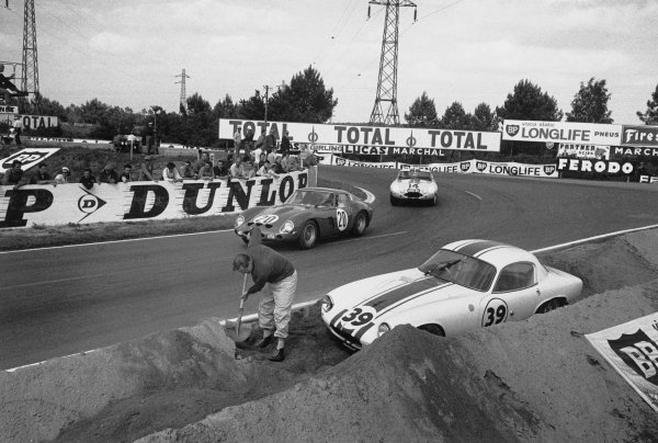 Le Mans, France. 15th - 16th June 1963 Fernand Tavano/Carlo Abate (Ferrari 250 GTO), retired, passes the beached John Wagstaff/Pat Fergusson (Lotus Elite Mk 14 Climax), 10th position, with Walt Hansgen/Augie Pabst (Jaguar E-type Light), retired, following, action. World Copyright: LAT Photographic Ref:  10451H - 35A.