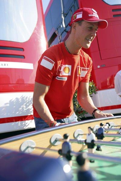 2006 British Grand Prix - Saturday Qualifying Silverstone, England. 8th - 11th June. Michael Schumacher, Ferrari 248F1, 2nd position, plays table football, portrait. World Copyright: Lorenzo Bellanca/LAT Photographic ref: Digital Image ZD2J3839