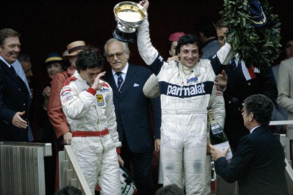 Riccardo Patrese celebrates victory alongside Andrea de Cesaris on the podium.