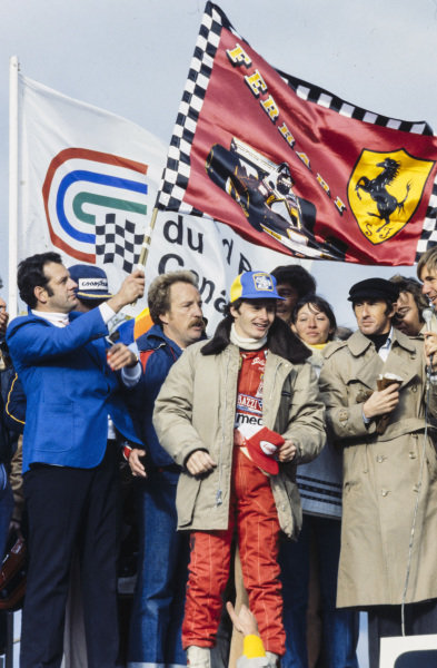 Gilles Villeneuve celebrates victory on the podium.