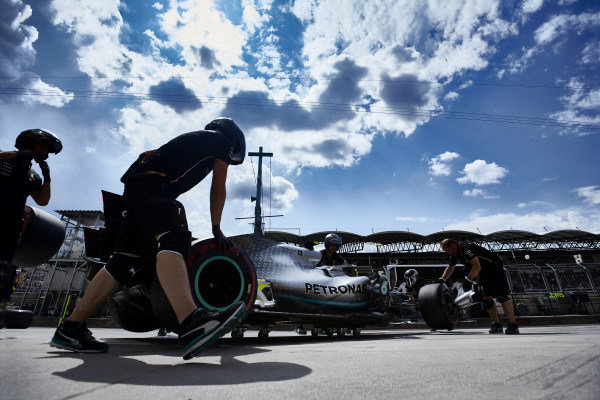Mechanics move Valtteri Bottas, Mercedes AMG W10, to the garage