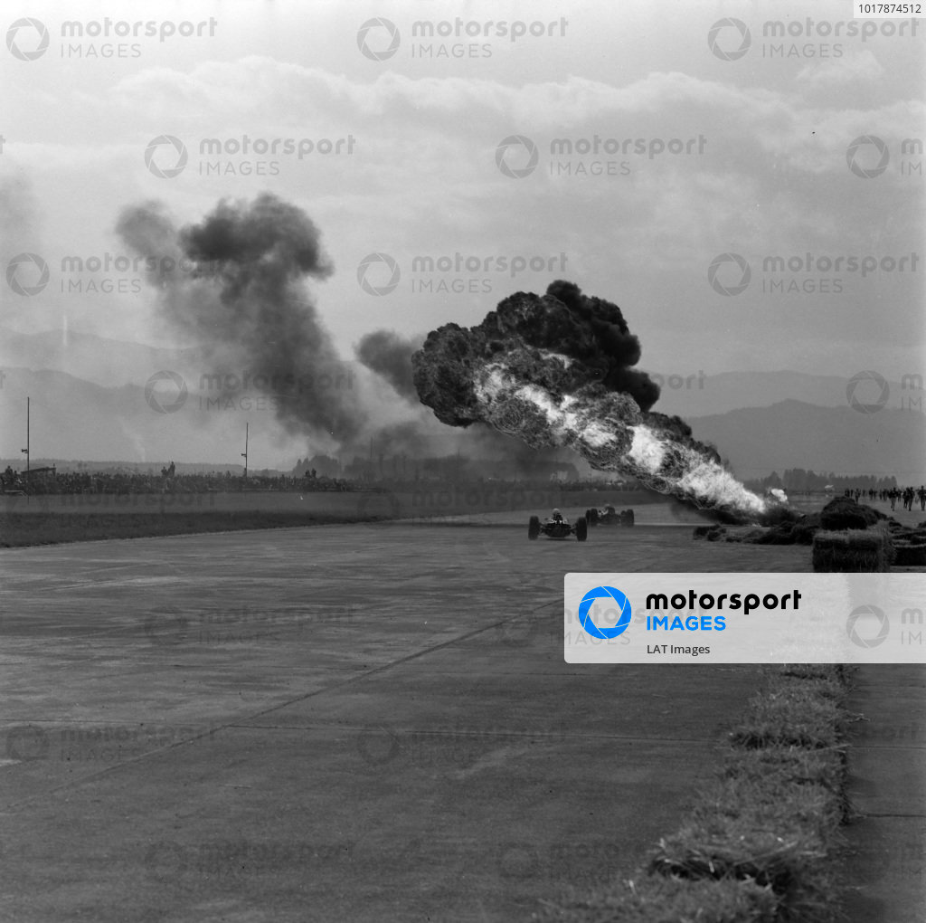 Cars approach the scene of the fiery accident involving Phil Hill, Cooper T66 Climax.