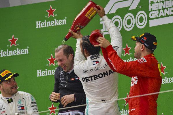 Valtteri Bottas, Mercedes AMG F1, 2nd position, the Mercedes Constructors trophy delegate, Lewis Hamilton, Mercedes AMG F1, 1st position, and Sebastian Vettel, Ferrari, 3rd position, on the dium
