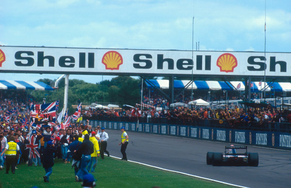 1992 British Grand Prix. Silverstone, England. 10-12 July 1992. The fans invade the track as Mansell mania hits its peak. Track stewards try in vain at the finish to hold them back and keep them from running into the way of the cars crossing the finish line. Ref-92 GB 16. World Copyright - LAT Photographic