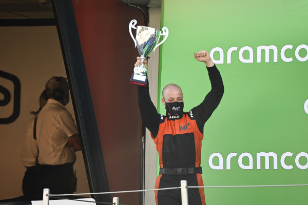 An MP Motorsport representative collects the teams trophy