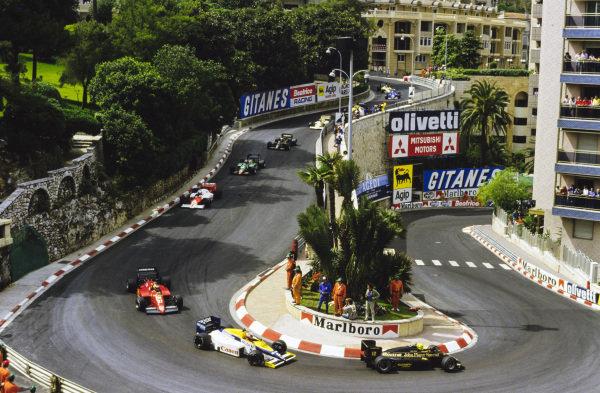 Ayrton Senna, Lotus 97T Renault, leads Nigel Mansell, Williams FW10 Honda, Michele Alboreto, Ferrari 156/85, Alain Prost, McLaren MP4-2B TAG, Eddie Cheever, Alfa Romeo 185T, and Elio de Angelis, Lotus 97T Renault, through Loews Hairpin on the opening lap.