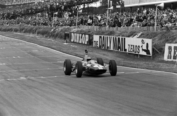 Jim Clark, Lotus 25 Climax, crossing the finish line at the end of the race.