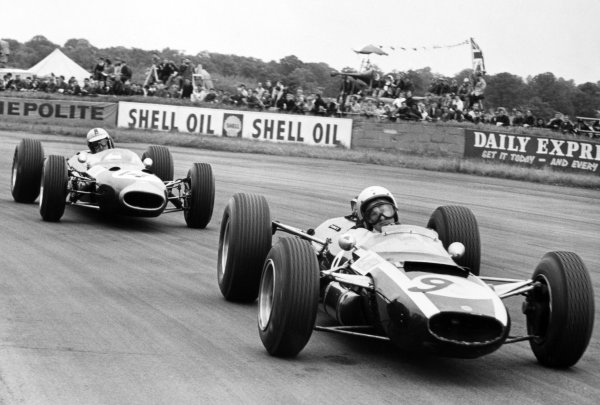 1965 British Grand Prix.Silverstone, Great Britain. 10 July 1965.Bruce McLaren, Cooper T77-Climax, 10th position, leads Denny Hulme, Brabham BT7-Climax, retired, action.World Copyright: LAT Photographic