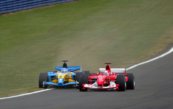 Michael Schumacher (GER) Ferrari F2003-GA runs Fernando Alonso (ESP) Renault R23B onto the grass on the run down to Stowe corner on lap one.