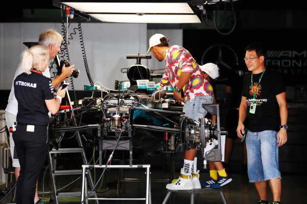 Sepang International Circuit, Sepang, Malaysia. Thursday 28 September 2017. Lewis Hamilton, Mercedes AMG, wears a colourful shirt whilst being photographed adjusting something in his cockpit by Steve Etherington.  World Copyright: Zak Mauger/LAT Images  ref: Digital Image _X0W6789