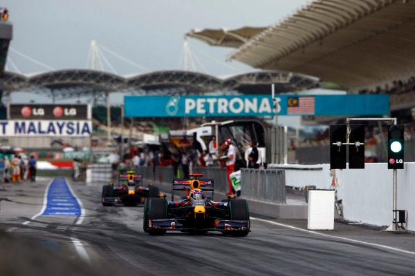 Sepang, Kuala Lumpur, Malaysia4th April 2009Mark Webber, Red Bull Racing RB5 Renault, leads Sebastian Vettel, Red Bull Racing RB5 Renault, out of the pits. Action. Pit Stops. World Copyright: Charles Coates/LAT Photographicref: Digital Image _26Y6115